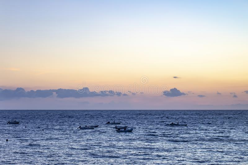 The abandoned fishing boats drifting in the sea during sunset along the coast of La Caleta, Costa Adeje on Tenerife, Spain.  stock photography