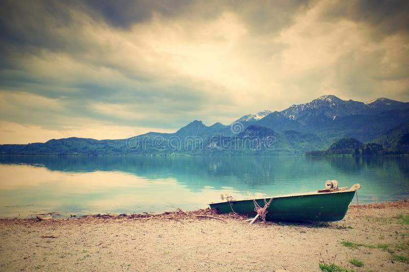 Abandoned fishing paddle boat on bank of Alps lake. Morning lake glowing by sunlight. Dramatic and picturesque scene. Mountains in water mirror royalty free stock photo