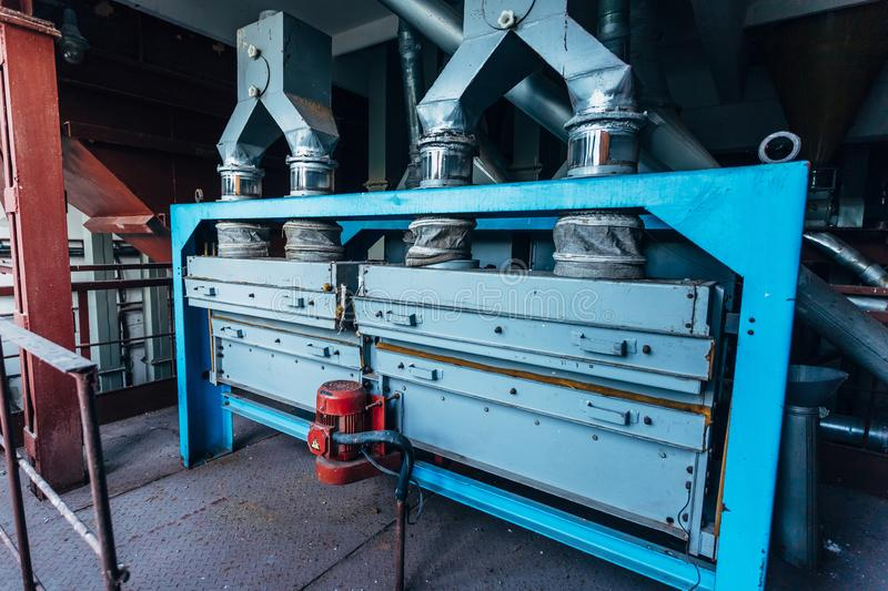 Abandoned flour milling factory. Old rusty grain cleaning air separation machines.  royalty free stock image