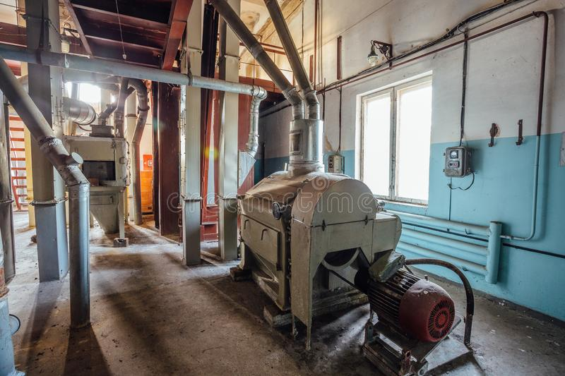 Abandoned flour milling factory. Old rusty roller mill equipment with pipeline.  royalty free stock photo