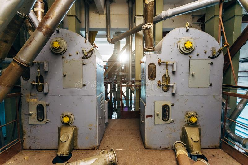 Abandoned flour milling factory. Old rusty roller mill equipment with pipeline.  stock photos