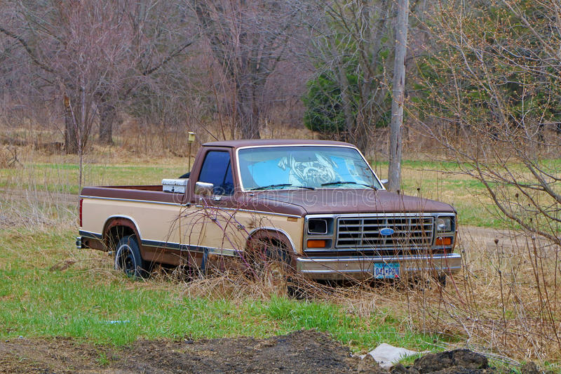 Abandoned Ford Truck Along the Road. This abandoned truck was parked along a roadside. It is rusted and has a sun shield in the front window. One of the stock photos