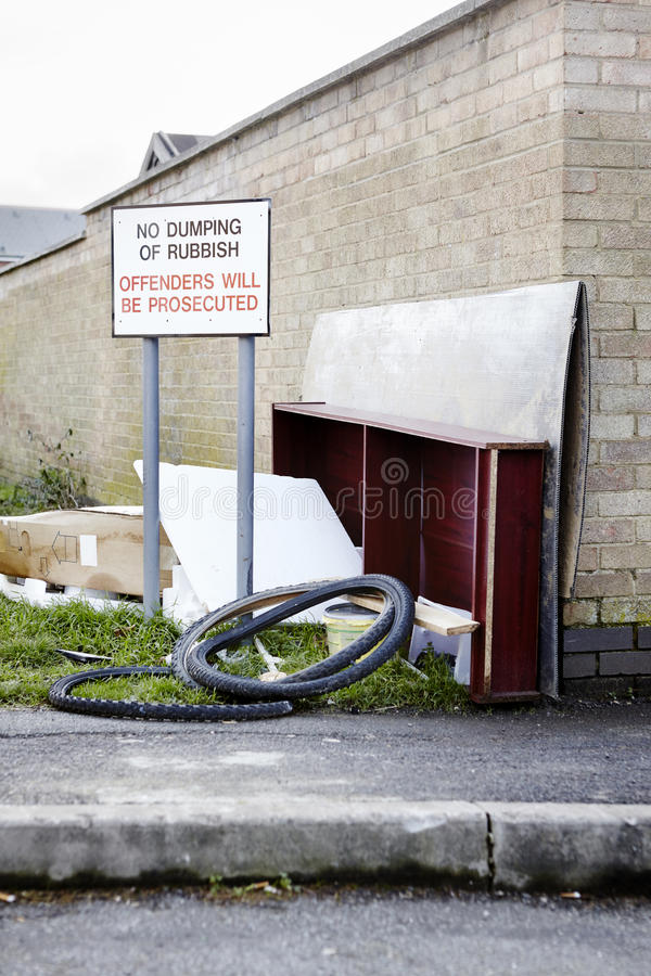 Abandoned garbage left next to no dumping sign. Abandoned garbage left next to no dumping of rubbish sign on street stock photography