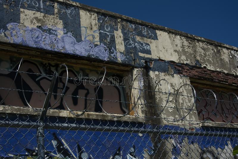 Abandoned Graffitied Building and Barbed Wire Coils on Sunny Day royalty free stock photo