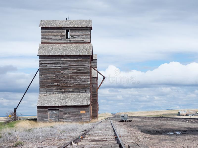 Abandoned Grain Elevator with Cloudy Skies. Abandoned wooden grain elevator in disrepair with train tracks leading up to it. Cloudy skies are behind. Image has stock image