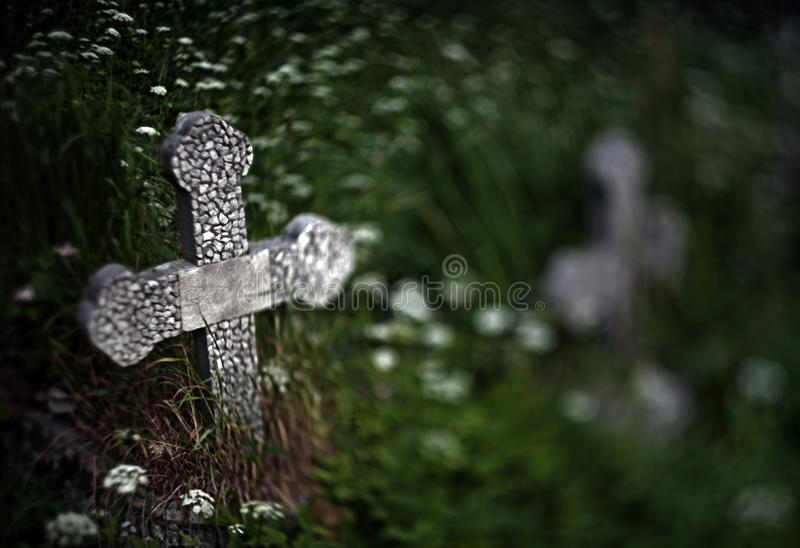 Abandoned grave cross on the blurred background of a grass and f royalty free stock images