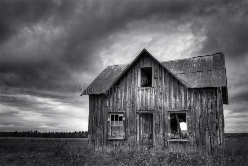 Abandoned Haunted Farm House with Stormy sky. Monochrome Abandoned Haunted Farm House with Stormy royalty free stock photography