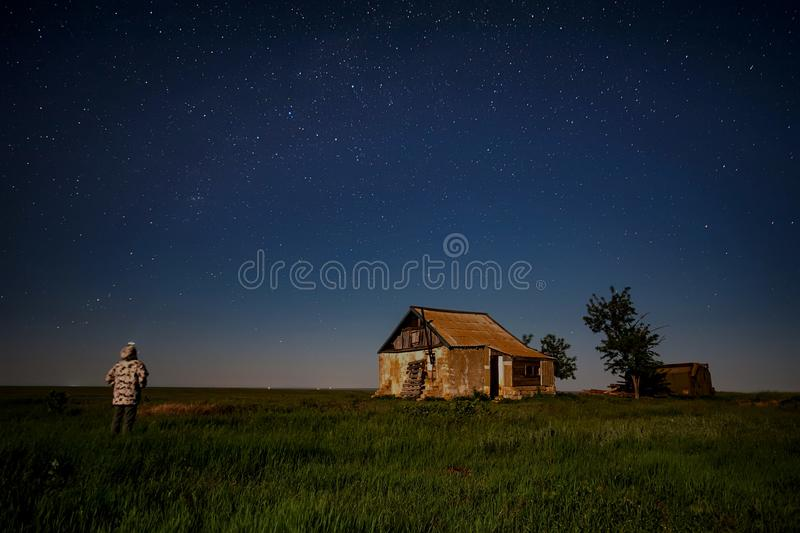 Night landscape with abandoned spooky house. Abandoned haunted house for night horror scene with a man in front stock images