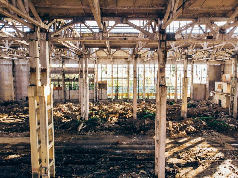 Abandoned and haunted industrial creepy warehouse inside, old ruined grunge factory building. Toned stock image