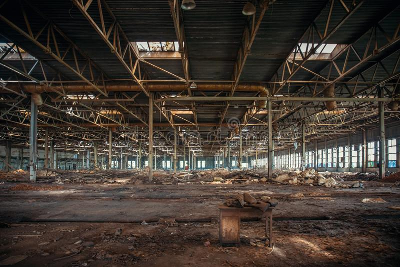 Abandoned and haunted industrial creepy warehouse inside, old ruined grunge factory building. Toned stock photo
