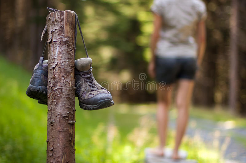 Abandoned hiking shoes. With a woman walking bare feet stock image