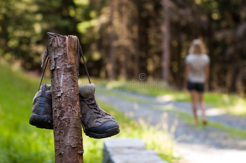 Abandoned hiking shoes. With a woman walking bare feet royalty free stock photo