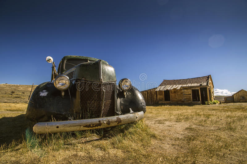 Abandoned historical car with main headlights and front grill royalty free stock photo