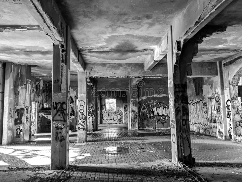 Abandoned Horse Barn. Monochrome image in black and white view of interior of an abandoned grungy old horse barn with graffiti and wet stone, falling ceilings stock photography