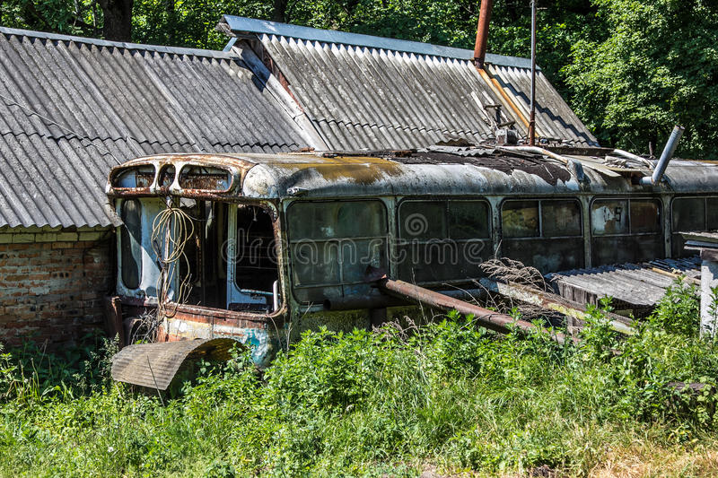 Abandoned house made of rusty old Soviet bus. Green post apocalypse concept stock photo