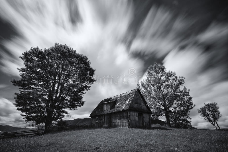 Abandoned house in West Ukraine.Old spooky abandoned farm house in black-white color. An old, long-abandoned house,against the bac. Kground of a cloudy sky, shot stock photo