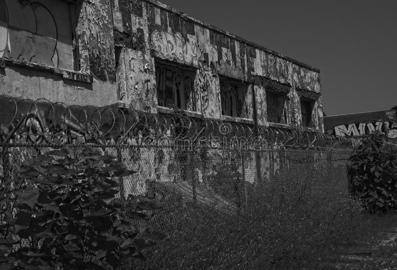 Abandoned Industrial Building and Barbed Wire Coils Black and White stock photo