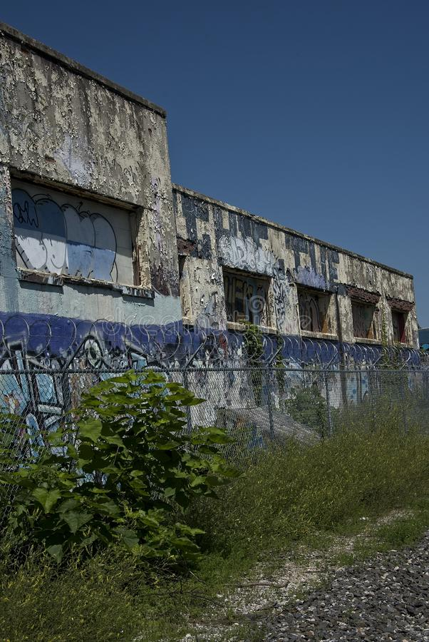 Abandoned Industrial Building with Graffiti and Barbed Wire Coils Vertical royalty free stock image