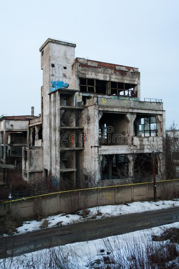 Abandoned industrial building with vegetation and graffiti royalty free stock photo