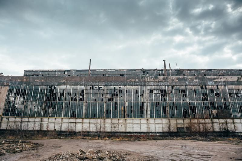 Abandoned industrial creepy warehouse, old dark grunge factory building. Toned royalty free stock photography