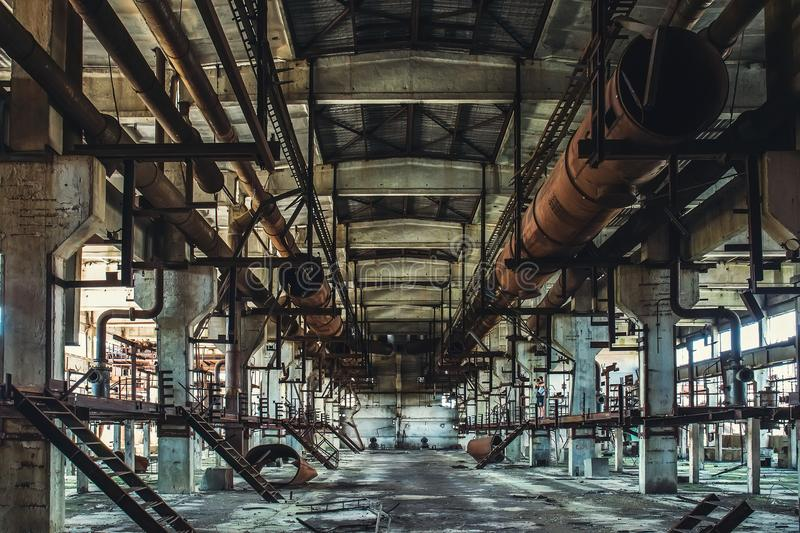 Abandoned Industrial workshop or hall of production for heavy industry factory . Huge steel pipes inside plant stock photo