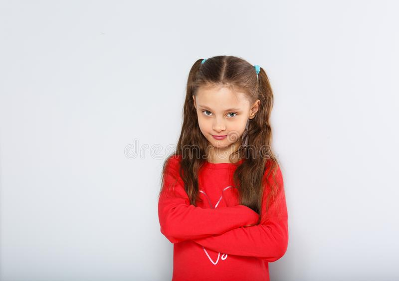 Abandoned kid girl in red Christmas blouse looking with double emotions, smiling and sad with folded arms. On blue background royalty free stock photography