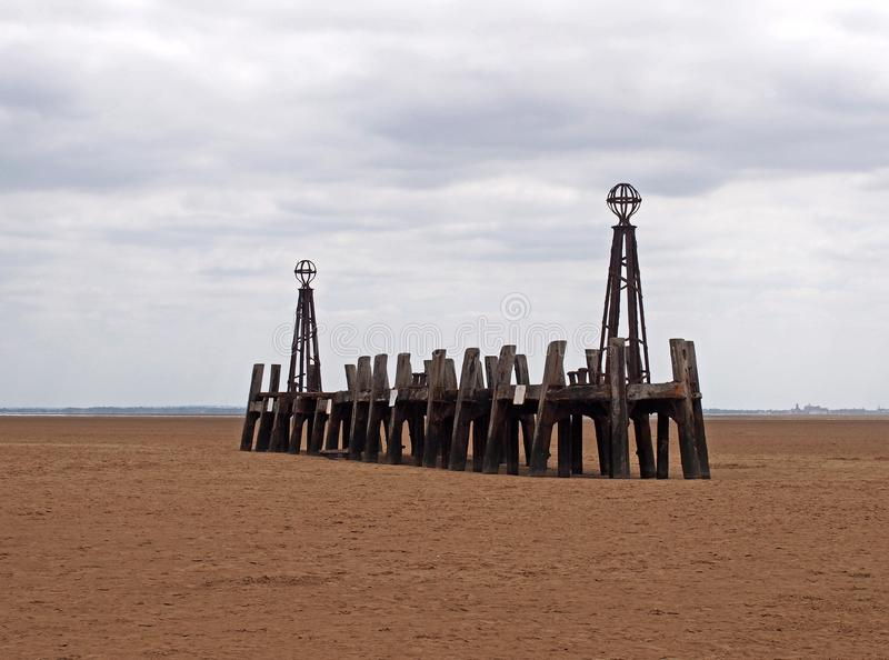 Abandoned landing stage at saint annes pier in the ribble estuary lancashire at low tide with grey clouds. The ruins of the abandoned landing stage at saint royalty free stock images