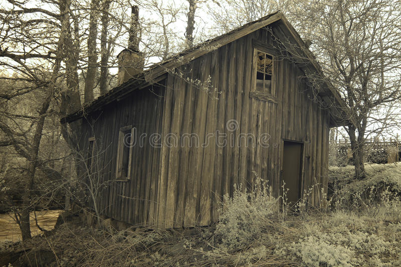 Abandoned lodging. A picture of an old, abandoned wooden house decaying in the woods royalty free stock photography