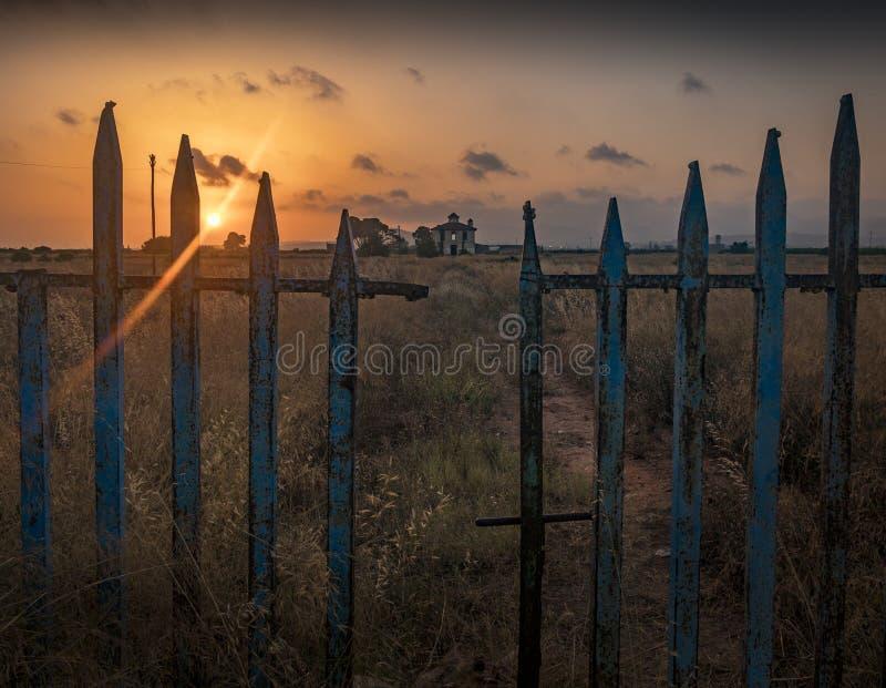 Abandoned mansion behind a broken fence in orange sunset stock images