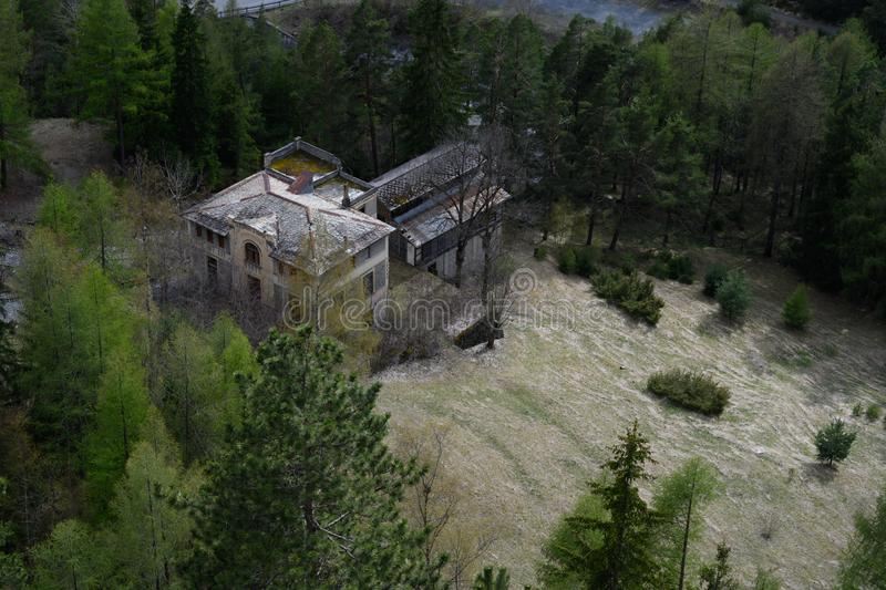 Abandoned mansion in the Italian Alps. Mansion on a steep mountain slope with fresh spring snow dusting it royalty free stock image