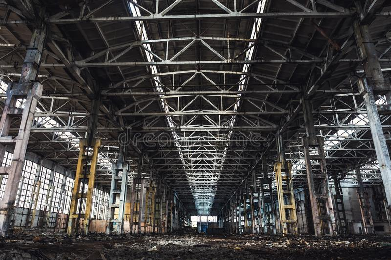 Abandoned metallurgical excavator plant or factory interior, industrial warehouse building waiting for a demolition. Toned royalty free stock image
