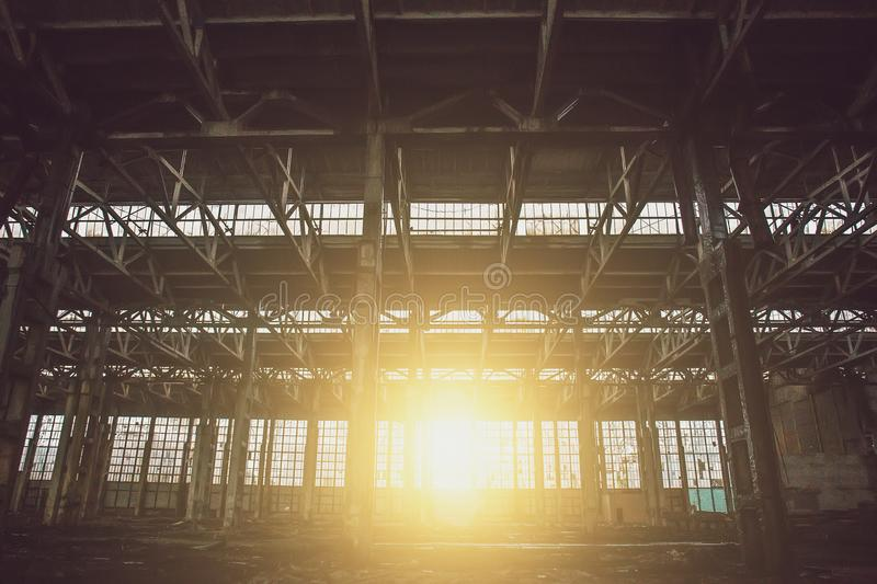 Abandoned metallurgical excavator plant or factory interior, industrial warehouse building waiting for a demolition. Sunset effect, toned stock photography