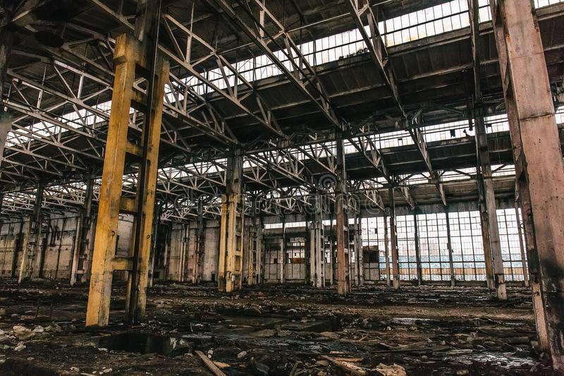 Abandoned metallurgical excavator plant or factory interior, industrial warehouse building waiting for a demolition. Toned royalty free stock images