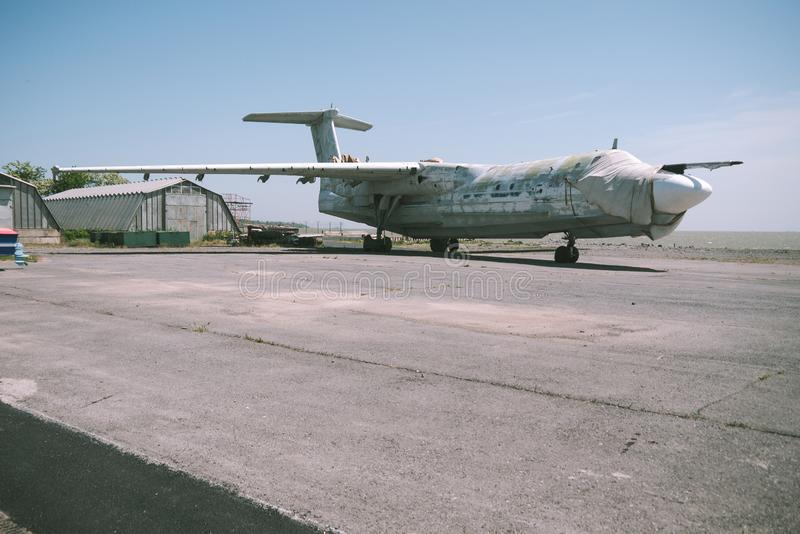 Abandoned military aircraft on an empty airfield near the hangar against the blue sky stock photos