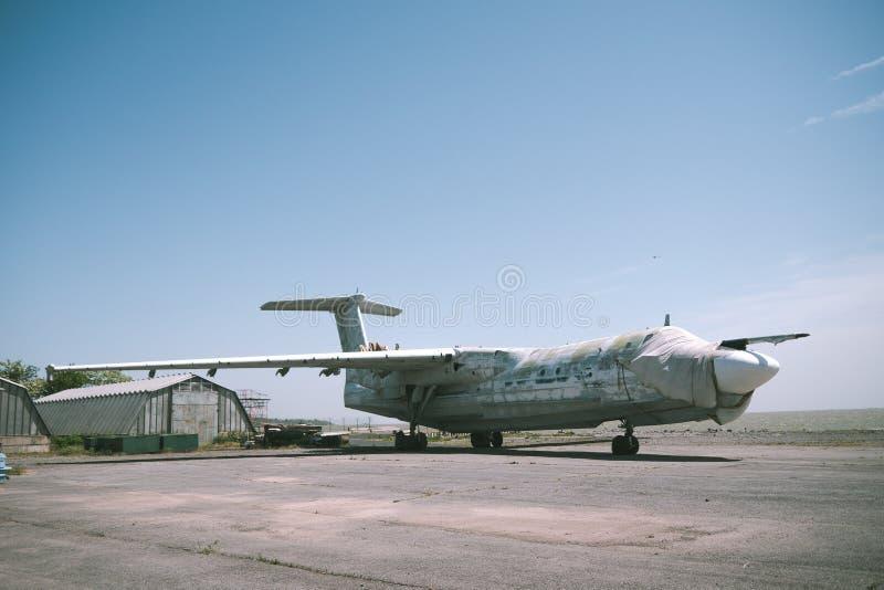 Abandoned military aircraft on an empty airfield near the hangar against the blue sky. stock photo