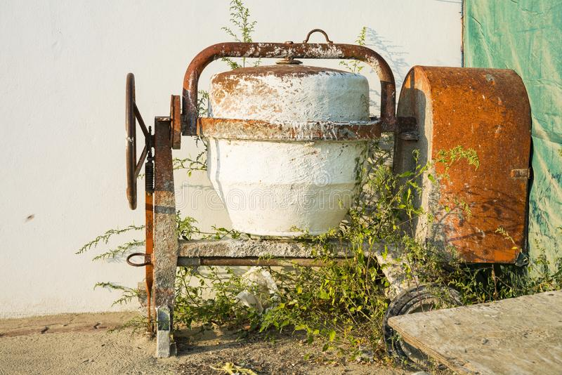 Abandoned mobile concrete mixer in garden. Mobile concrete mixer in messy sunny garden with twigs and leaves stock images
