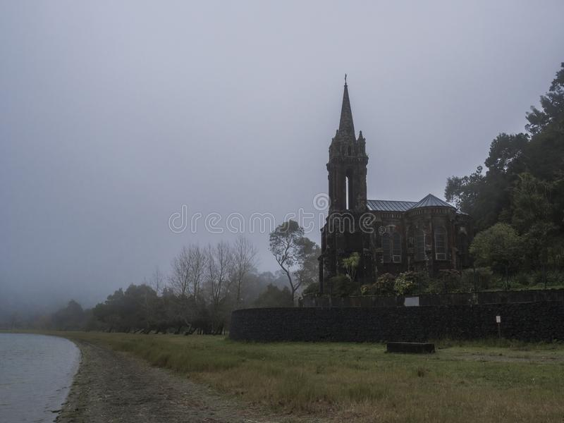 Abandoned Neogothic Chapel of Nossa Senhora das Vitorias at Furnas Lake bank in misty day, Sao Miguel, Azores, Portugal stock photos