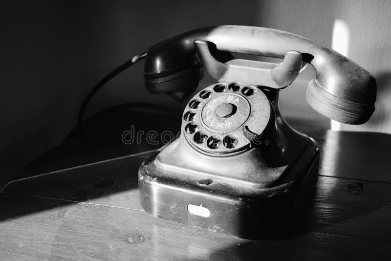 Abandoned nostalgic dial telephone in black and white. Abandoned nostalgic old style dial telephone in black and white stock image