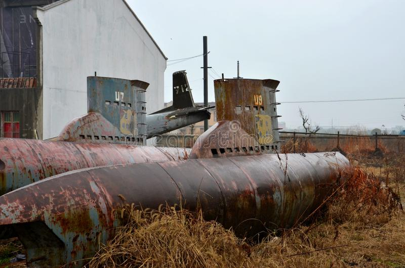 Abandoned obsolete submarines and airplane in junkyard stock images