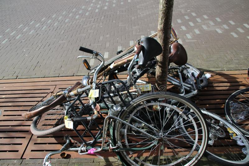 Abandoned and old bikes on the street which are marked with label to be removed by the municipality of Den Haag in the Netherlands royalty free stock image