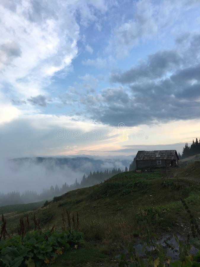 Abandoned old cabin isolated on a mountain under dark skies with a foggy background. An abandoned old cabin isolated on a mountain under dark skies with a foggy royalty free stock photography