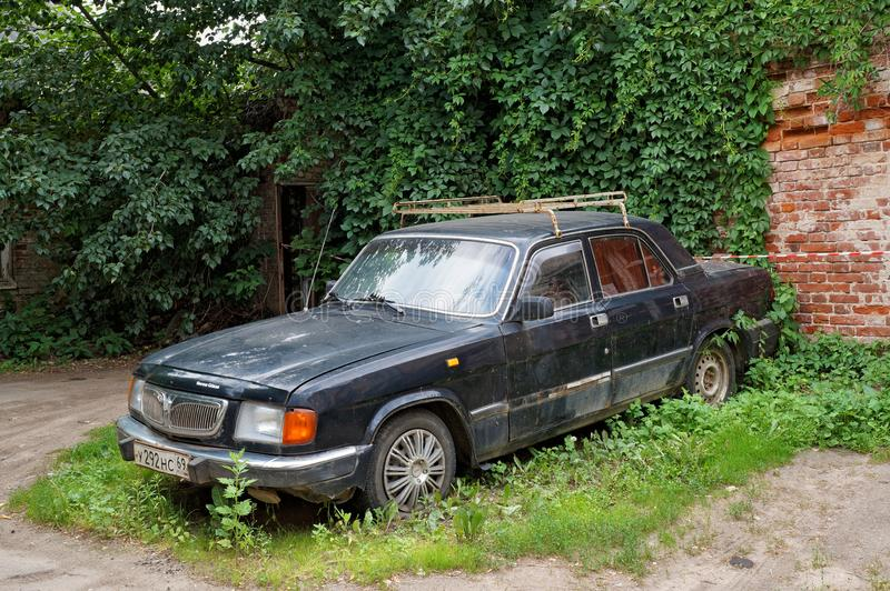 Abandoned old car GAZ-3102 `Volga` parked in the courtyard stock photos