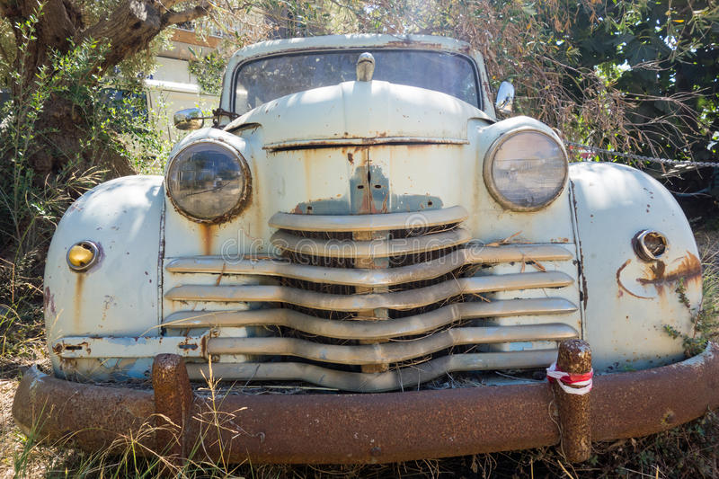 Abandoned Old Car. An abandoned 1950's car, with rusted metal and faded and flaked pastel green paint, parked amongst bushes and trees stock image