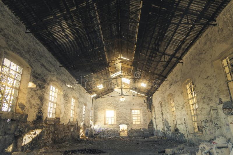 Abandoned old factory in Peñarroya Spain. The light goes through the roof and the windows of a building in an abandoned factory stock images