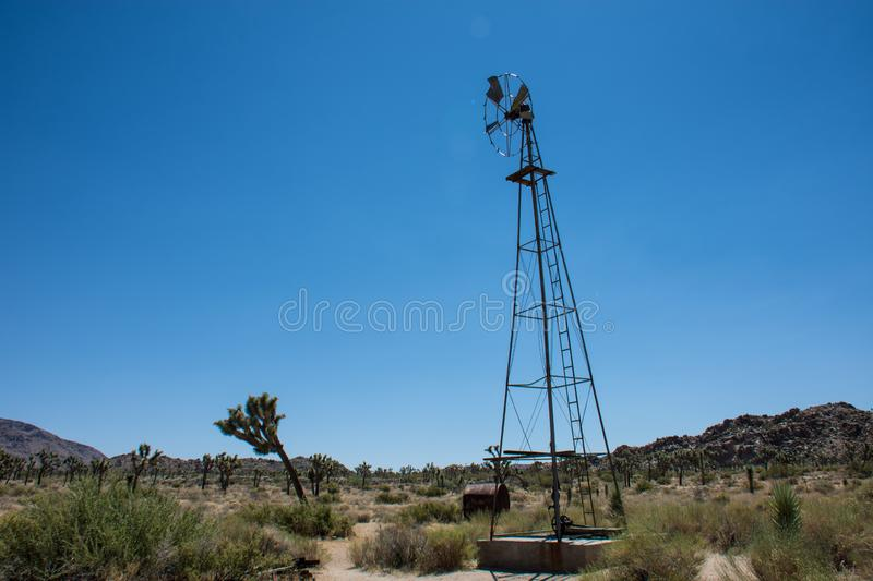Abandoned old fashioned windmill sits along the trail to the Wall Street Mill, a former mining operation in the desert stock photography