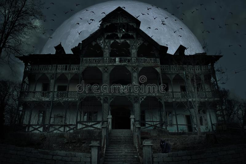 Abandoned old haunted house with dark horror atmosphere in the moonlight.  royalty free stock image