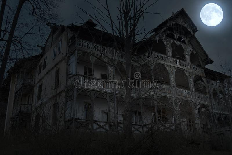 Abandoned old haunted house with dark horror atmosphere in the moonlight.  royalty free stock photo