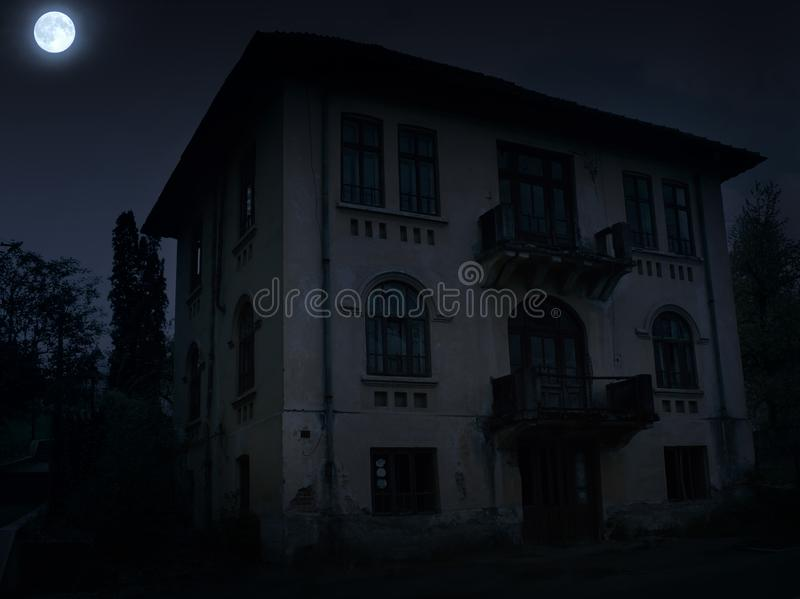 Abandoned old haunted house with dark horror atmosphere in the moonlight.  royalty free stock photos