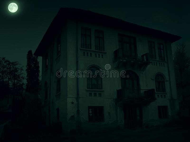 Abandoned old haunted house with dark horror atmosphere in the moonlight.  royalty free stock images