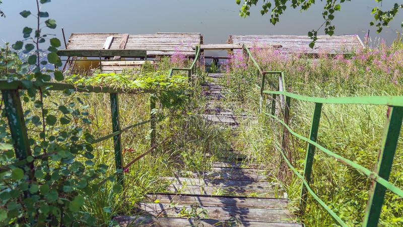 Abandoned old metal stairs to water of country river royalty free stock photos